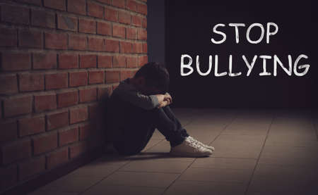 Message STOP BULLYING and sad little boy sitting on floor near brick wall indoors 写真素材