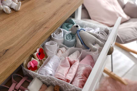 Modern open chest of drawers with baby clothes and accessories in room, closeup
