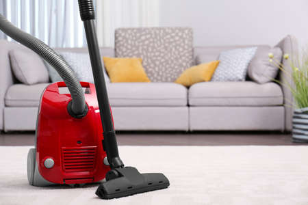 Modern red vacuum cleaner on carpet indoors, space for text