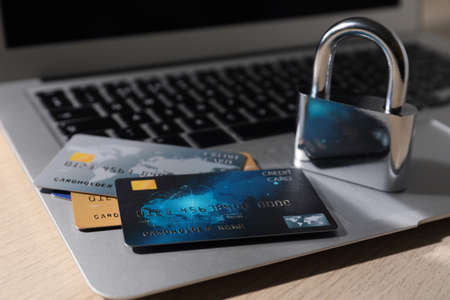 Credit cards, lock and laptop on wooden table, closeup. Cyber crime