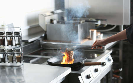 Female chef cooking meat with burning flame on stove in restaurant kitchen, closeup