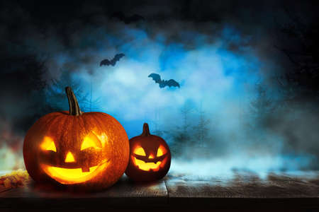 Scary Jack O Lantern pumpkins and flying bats in misty forest on Halloween. Space for text