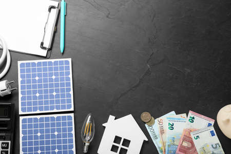 Flat lay composition with solar panels and money on black table. Space for text