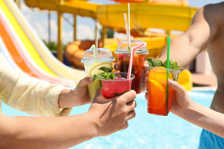 People with refreshing drinks in water park, closeup