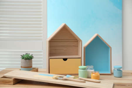 House shaped shelves, brushes and jars of paints on table indoors