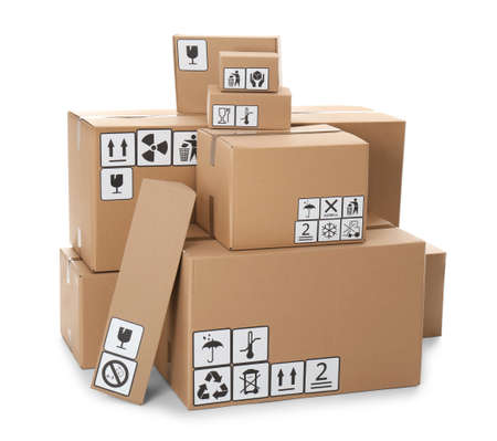 Stacks of cardboard boxes with different packaging symbols on white background. Parcel delivery