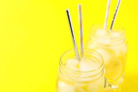 Closeup view of natural lemonade on yellow background, space for text. Summer refreshing drink Imagens