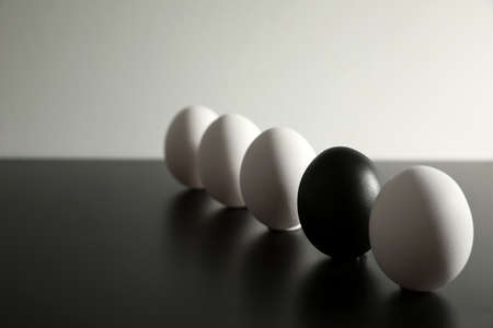 Black egg among others on table. Space for text