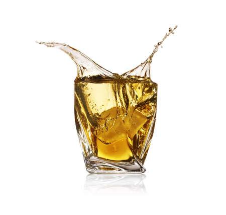 Whiskey splashing in glass on white background Imagens