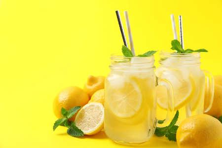Freshly made natural lemonade on yellow background. Summer refreshing drink