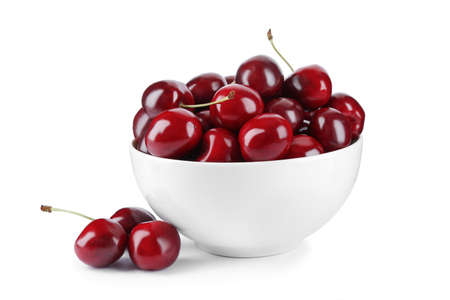 Tasty ripe red cherries and bowl isolated on white