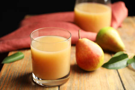 Fresh pear juice in glass and fruits on wooden table, closeup