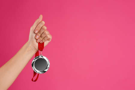 Woman holding silver medal on pink background, closeup. Space for design