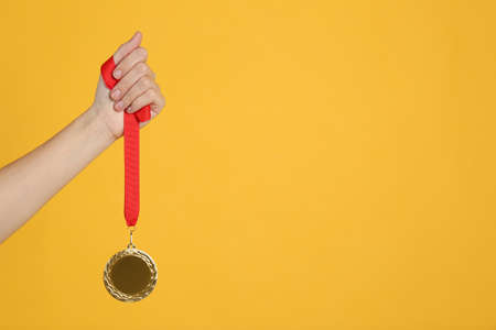 Woman holding golden medal on yellow background, closeup. Space for design
