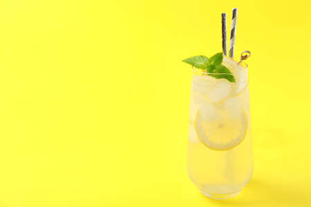 Natural lemonade on yellow background, space for text. Summer refreshing drink