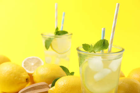 Natural freshly made lemonade with mint on yellow background, closeup. Summer refreshing drink Imagens