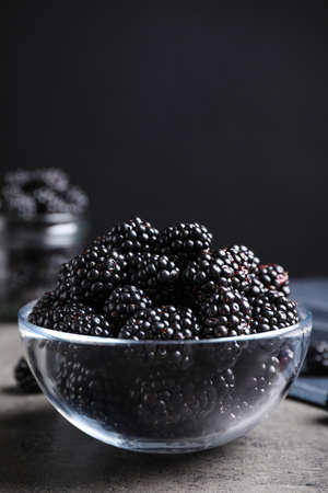 Delicious fresh ripe blackberries in glass bowl on gray table. Space for text