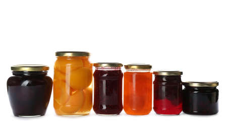 Glass jars with different pickled fruits and jams on white background