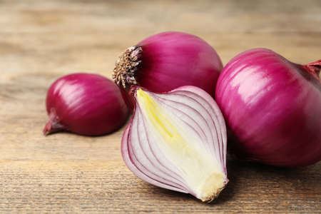 Ripe red onion bulbs on wooden table, closeup Imagens