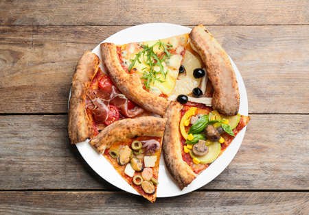 Slices of different pizzas on wooden table, top view Zdjęcie Seryjne