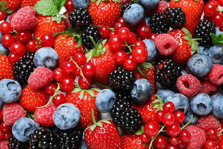 Mix of fresh delicious berries as background, top view