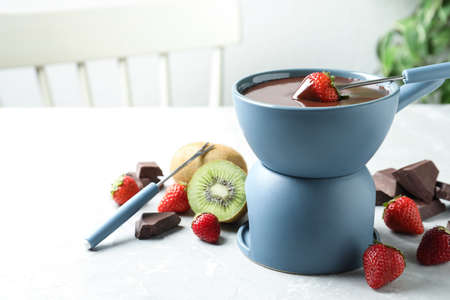 Dipping strawberry into fondue pot with chocolate on light marble table Imagens