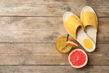 Slide sandals, cocktail, grapefruit and space for text on wooden background, flat lay. Beach objects