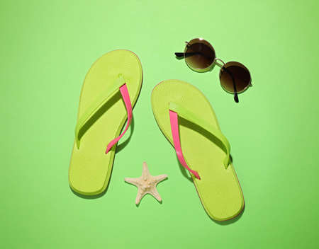 Flat lay composition with beach fashion objects on green background