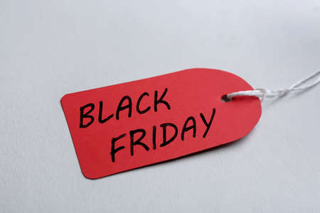 Red blank tag on light background, closeup. Black Friday concept