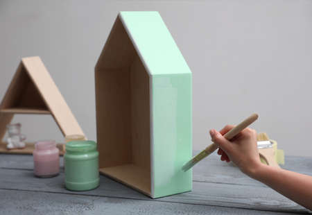 Woman painting wooden house model at gray table, closeup
