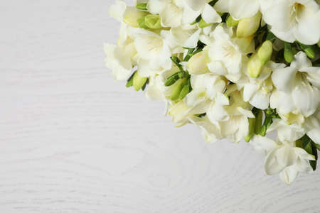 Beautiful freesia flowers on white wooden background, above view. Space for text Standard-Bild