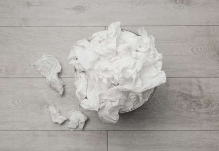 Used paper tissues and trash can on wooden floor, flat lay