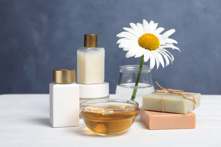Composition with chamomile flower and cosmetic products on white wooden table Banque d'images