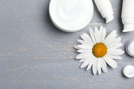 Flat lay composition with chamomile flower and cosmetic products on wooden table, space for text