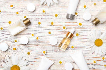 Flat lay composition with chamomile flowers and cosmetic products on white wooden table