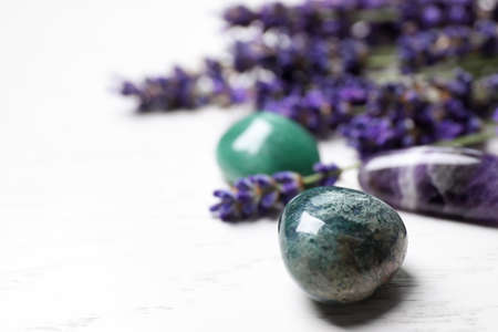 Gemstones and healing herbs on white wooden table, closeup. Space for text Banque d'images