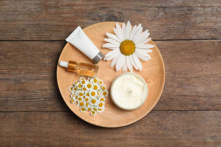 Composition with chamomile flowers and cosmetic products on wooden table, top view Banque d'images