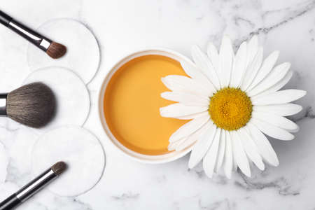 Flat lay composition with chamomile flower and cosmetic product on white marble table