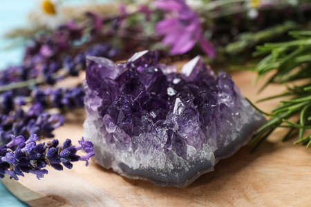 Amethyst and healing herbs on wooden board, closeup