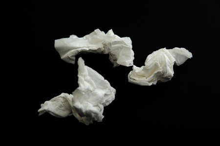 Used white paper tissues on black background