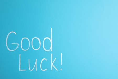 Phrase GOOD LUCK on light blue background, top view. Space for text