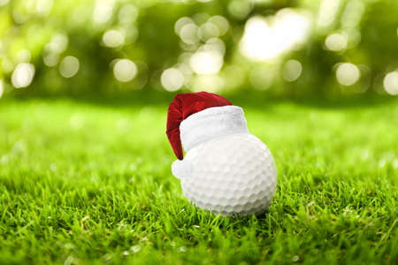 Golf ball with small Santa hat on green course
