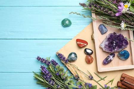 Gemstones and healing herbs on light blue wooden table, flat lay. Space for text