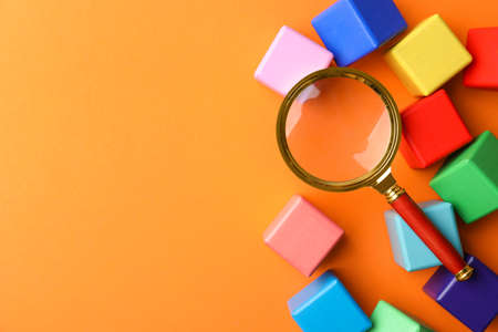 Different colorful cubes and magnifier glass on orange background, flat lay with space for text. Find keywords concept