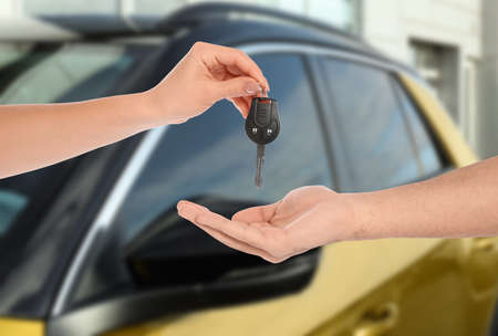 Car buying. Woman giving key to new owner against blurred automobile, closeup