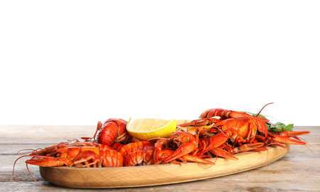 Delicious boiled crayfishes on wooden table against white background Фото со стока