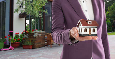 Real estate agent with model against modern house, space for text. Banner design, closeup