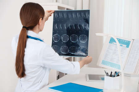 Orthopedist examining X-ray picture at desk in clinic Stockfoto