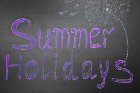 Phrase SUMMER HOLIDAYS written on black background. School's out
