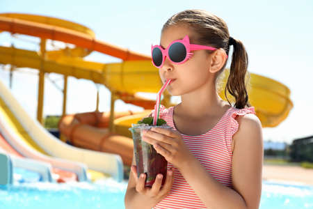 Girl with delicious refreshing drink in water park